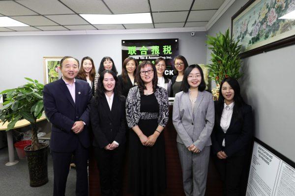 联合报税公司总经理Sarah Jia(中)与副总经理Mark Jia(前排左一)与员工合照
